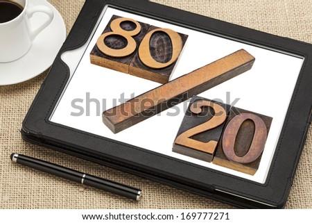 Pareto principle or eighty-twenty rule represented in wood letterpress printing blocks on a digital tablet screen
