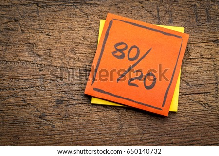 Pareto principle or eighty-twenty rule represented on a sticky note against rustic wood - a reminder or advice #650140732