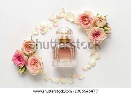 Parfume bottle with roses on white background. Top view.