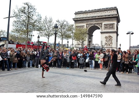 PARIS - APRIL 27: B-boy doing some breakdance moves in front a street crowd, at Arch of Triumph, April 27 2013, Paris, France