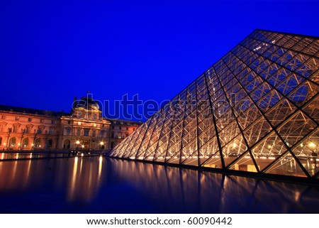 PARIS - APRIL 16: Closeup of Louvre Pyramid shines at dusk during the Summer Exhibition April 16, 2010 in Paris. This is one of the most popular tourist destinations in France.