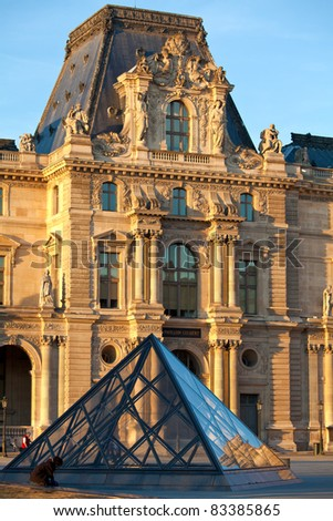 PARIS - APRIL 6: Louvre museum and Pyramid  before sunset on April 06, 2011 in Paris. Louvre is most visited museum in the world with 8.5 million visitors per year. - stock photo