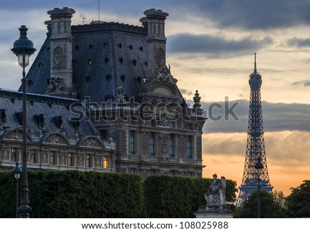PARIS-APRIL 29: Right wing of Louvre Museum and Eiffel Tower at dusk on April 29, 2009, Paris, France. These famous landmarks are most visited museums in world with about 6 million visitors every year
