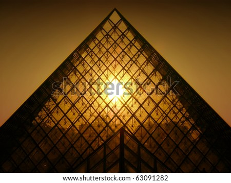 PARIS- APRIL 8 : Sunset shines through the glass pyramid of the Louvre museum on April 8, 2007 in Paris.