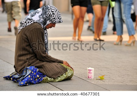 PARIS - AUGUST 22: An unidentified female begs on the street in the Champs-Elysees on August 22, 2009 in Paris, France. The number of beggars is considerably higher due to the current economics.