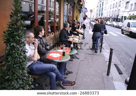 PARIS - AUGUST 24 : Parisians enjoy summer evening drinks in cafe sidewalk in Paris, France on August 24, 2007. Paris is one of the most populated metropolitan areas in Europe.