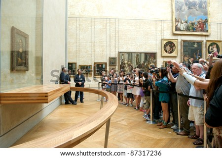 "PARIS - AUGUST 4: Visitors take photo of Leonardo DaVinci's ""Mona Lisa"" at the Louvre Museum, August 4, 2011 in Paris, France. The painting is one of the world's most famous."