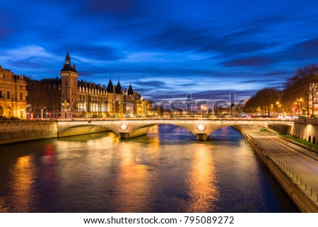 Paris city center by night with embankments of river Seine and illuminated street and historical Parisian building of Conciergerie on City island, blue hour, France. Photo stock ©