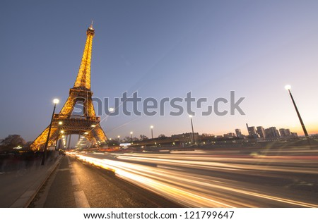 PARIS - DEC 1: Cars speed up in Pont D'Iena with Eiffel Tower in background, December 1, 2012 in Paris. The Tower is the tallest monument in Paris and one of the most visited in the World.