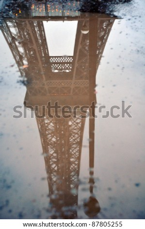PARIS - DEC, 29: Eiffel Tower Reflection in a puddle at dusk, closeup on December 29, 2010 in Paris. Eiffel Tower is the highest monument in France use 20,000 light bulbs in the show.