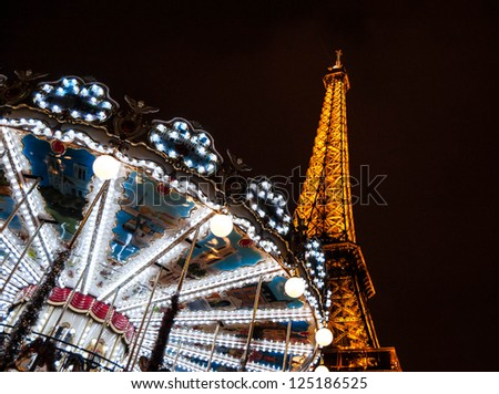 PARIS - DECEMBER 29: Eiffel Tower and antique carousel as seen at night on December 29, 2012 in Paris, France. The Eiffel tower is the most visited paid monument in the world.