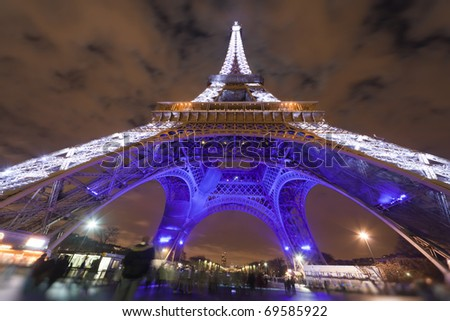 PARIS - DECEMBER 29: Eiffel Tower illuminated at night on background of cloudy sky, view from below,  December 29, 2009, Paris, France. This is the most recognizable architectural landmark in Paris.