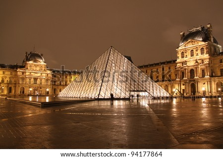PARIS - DECEMBER 9: Louvre museum in Paris, France at night on December 9, 2009. Louvre is the biggest museum in Paris with over 60,000 square meters of exhibition space. - stock photo