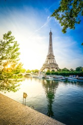 Paris Eiffel Tower and river Seine at sunrise in Paris, France. Eiffel Tower is one of the most iconic landmarks of Paris, retro toned