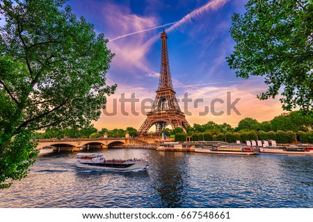 Paris Eiffel Tower and river Seine at sunset in Paris, France. Eiffel Tower is one of the most iconic landmarks of Paris. #667548661