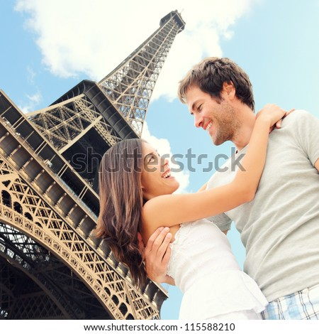 Paris Eiffel tower romantic couple embracing kissing in front of Eiffel Tower, Paris, France. Happy young interracial couple, Asian woman, Caucasian man.