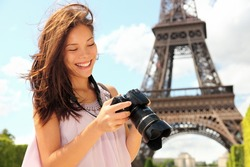 Paris Eiffel Tower tourist with camera taking pictures in front of the Eiffel tower, Paris, France. Young photographer woman in her 20s.