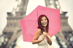 Paris Eiffel Tower Woman happy smiling in front of tourist attraction Eiffel Tower. Joyful fresh Caucasian Asian girl laughing.