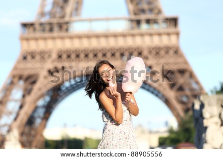 Paris Eiffel Tower woman smiling happy and cheerful eating cotton candy in front of Eiffel Tower in Paris, France. Cute Asian / Caucasian girl.