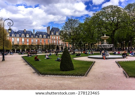PARIS, FRANCE - APRIL 12, 2015: People relaxing on green lawns of famous Place des Vosges - oldest planned square in Paris, in Marais district. Place des Vosges was built by Henri IV from 1605 to 1612