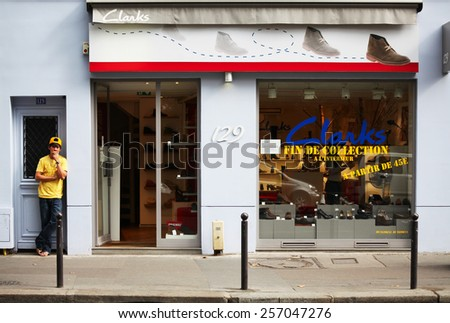 PARIS, FRANCE - AUGUST 31, 2012: Young man is waiting next to a Clarks store in Paris, France. He`s waring clothes in the same color as the text on the store.