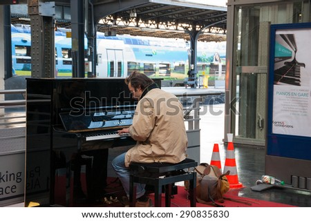 PARIS, FRANCE - DECEMBER 15, 2013: Man playing piano at Gare de l\'Est (Paris Est train station). Several pianos are found at Parisian train stations allowing the passengers to play for their pleasure.
