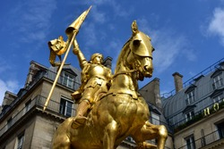 Paris, France. Jeanne d'Arc (Joan of Arc) golden statue. Blue sky with white clouds.