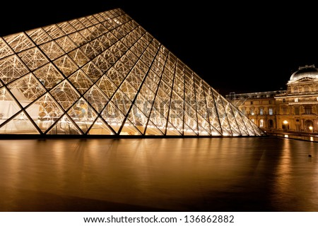 PARIS, FRANCE - MARCH 8: Pyramid of Louvre Museum at night. in 1983 architect I. M. Pei was proposed a glass pyramid to stand over a new entrance in the main court, in Paris on March 8, 2013 - stock photo
