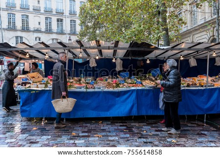 Paris, France -- November 4, 2017 -- Shoppers look over an outdoors  Parisan fish market stand. Editorial Use Only.