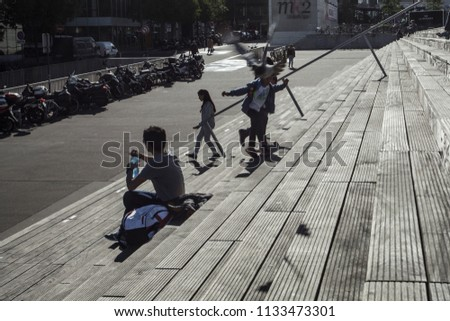 Paris, France -October 5,  2016: French National Library towers in Paris and the stairs to the plaza on a sunny day, people reading on the wooden stairs