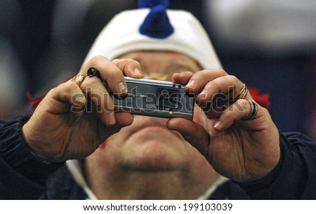 PARIS, FRANCE-OCTOBER 14, 2007: french rugby fan taking picture with an handy camera during the Rugby World Cup match France vs England, in Paris.