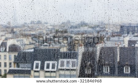 PARIS, FRANCE, on AUGUST 27, 2015. A look through a wet window. to roofs of the city7 It is raining, water drops on glass, focus on drops