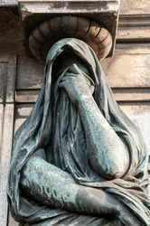 Paris, France. Père Lachaise Cemetery. A statue depicting a woman taken from sadness and despair.