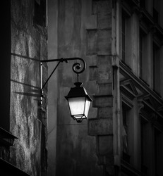 Paris, France. Parisian street at evening. Lantern hanging from the building wall. Black and white photo.