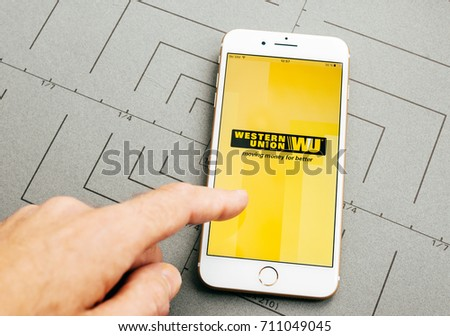 PARIS, FRANCE - SEP 26, 2016: Male hand holding New Apple iPhone 7 Plus after unboxing and testing by installing the app application software Western Union money transfer app