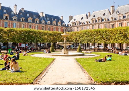 PARIS FRANCE SEPTEMBER 24 People relaxing on green lawns of the famous Place des Vosges the oldest planned square in Paris located in Marais district on September 24 2013 in Paris
