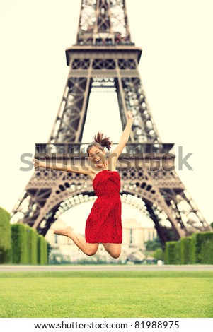 Paris girl at Eiffel Tower jumping happy smiling excited in red summer dress. Joyful young woman on Champs cheerful during vacation / holidays in Paris, France, Europe. - stock photo