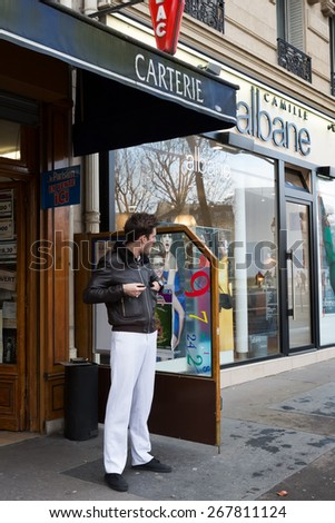 PARIS-JAN 4, 2014: A man smokes a cigarette outside a tabac shop, a store licensed to sell tobacco products. Tabacs are identified by a distinctive elongated diamond sign in red.