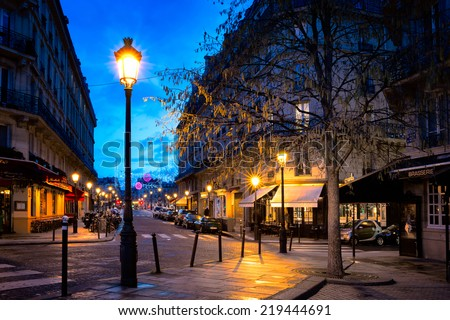 PARIS-JAN 5,2014:Paris street in one of the oldest neighborhoods in the city, the Ile Saint-Louis, with cobblestone streets and charming buildings lit by street lamps. Shot in the blue hour.