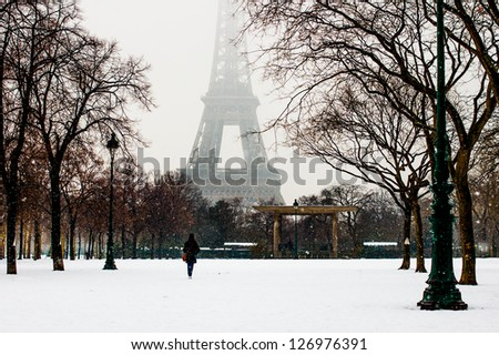 PARIS - JANUARY 19: Eiffel tower and champ de Mars in snow on January 19, 2013 in Paris. Snowfall is rare, but beautiful event in the city,