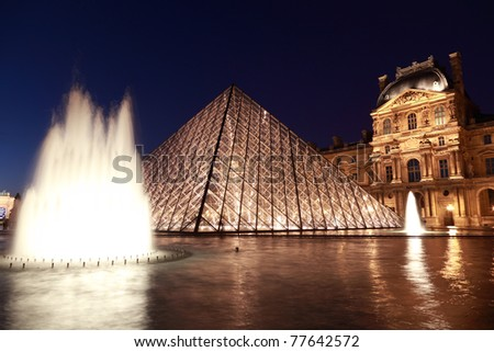 PARIS - JANUARY 1: Louvre Pyramid and Pavillon Rishelieu in the evening, January 1, 2010, Paris, France. Pavillon Rishelieu is the one of four parts of Louvre museum. - stock photo