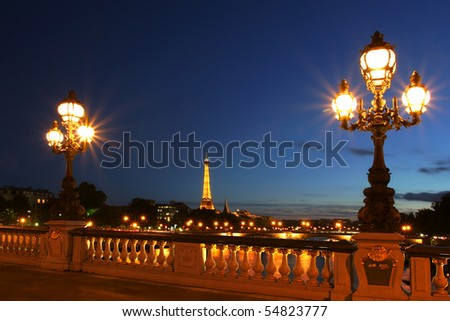 PARIS - JULY 10: Famous Eiffel Tower with night illumination and beautiful lampposts on Alexander the Third (Alexander III) bridge on July 10, 2007 in Paris, France. The Eiffel Tower is the most visited monument in France