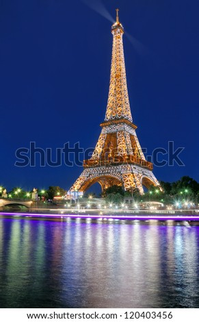 PARIS - JULY 30: The illuminated Eiffel Tower and river Seine on July 30, 2012 in Paris, France. The Eiffel Tower is most famous sights of Paris.