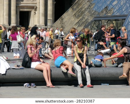 PARIS - JULY 4: Tourists rest near the Louvre on July 4, 2008 in Paris. The Louvre was once a palace and is now a museum.