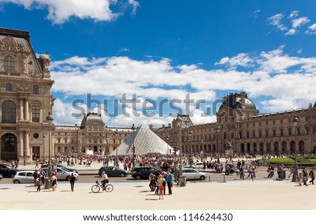 PARIS - JULY 14: Tourists walk near the Louvre on July 14, 2012 in Paris. The Louvre was once a palace and is now a museum.