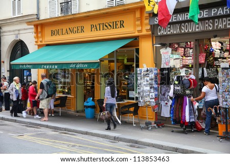 PARIS - JULY 21: Tourists walk past a souvenir store on July 21, 2011 in Paris, France. Paris is the most visited city in the world with 15.6 million international arrivals in 2011.