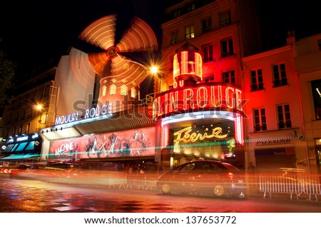 PARIS - JUNE 5 - Moulin Rouge by night photographed with a long exposure with traffic blurring by June 5, 2013, Paris, France. Moulin Rouge (French for Red Mill) is a cabaret in Paris, France.