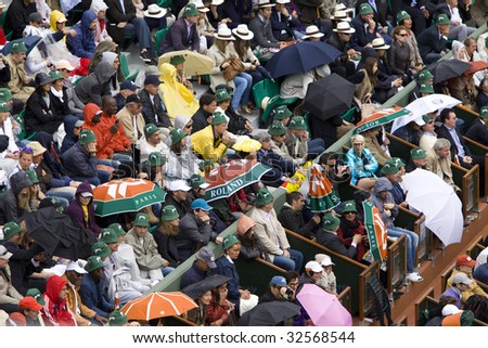 PARIS - JUNE 7: Spectators with umbrellas and rain coat watch a tennis match at Roland Garros French Open tennis tournament on June 7, 2009 in Paris.