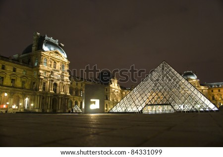 PARIS - MARCH 20: Louvre Pyramid shines at night during the winter March 20, 2008 in Paris. Louvre is the biggest Museum in Paris displaying over 60,000 square meters of exhibition space. - stock photo
