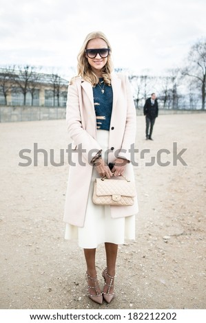 PARIS MARCH 1 2014 Stylish European woman with sunglasses and Coco Chanel bag in the Tuileries Garden Paris Fashion Week Ready to Wear 2014 2015 is held from February 25 to March 5 2014